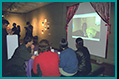 Spectators07: Spectators watch the groom 'on stage' (blonde hair) interacting with world cyber participants while he is physically on the other side of the lobby (to take their live suggestions).